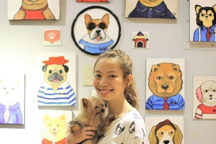 veterinary student holding a dog and drawings on the wall