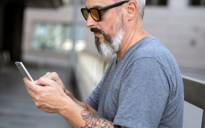 Man sitting on the bench and looking at mobile phone as a way to use pet missing apps - I Love Veterinary