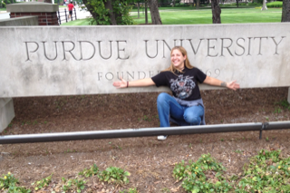 Natasha Feduik in front of the sign of Purdue University - I Love Veterinary