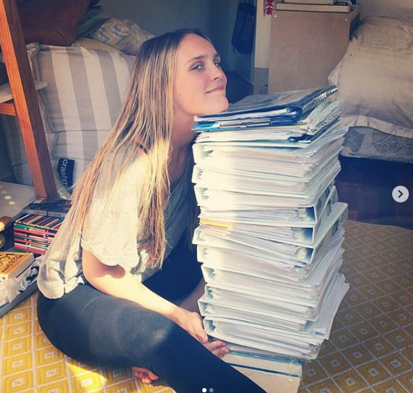 Dr. Chloe Buiting with the pile of books while she was on her studies - I Love Veterinary