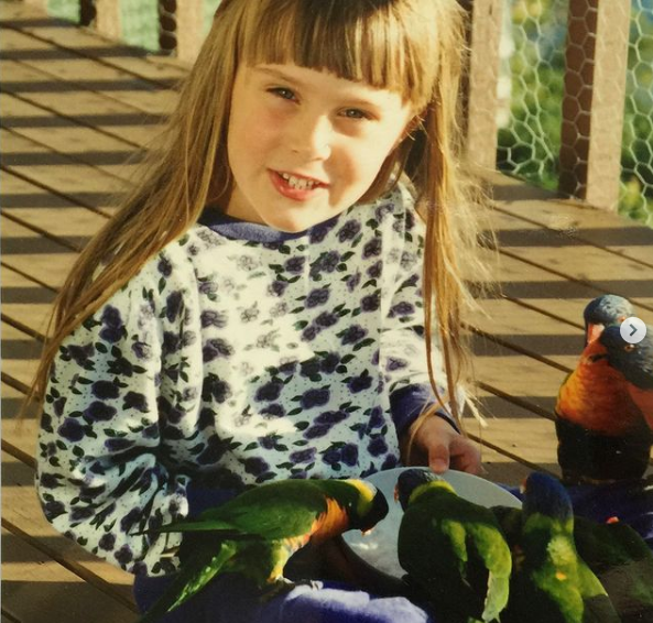 Dr. Chloe Buiting as a child feeding parrots - I Love Veterinary